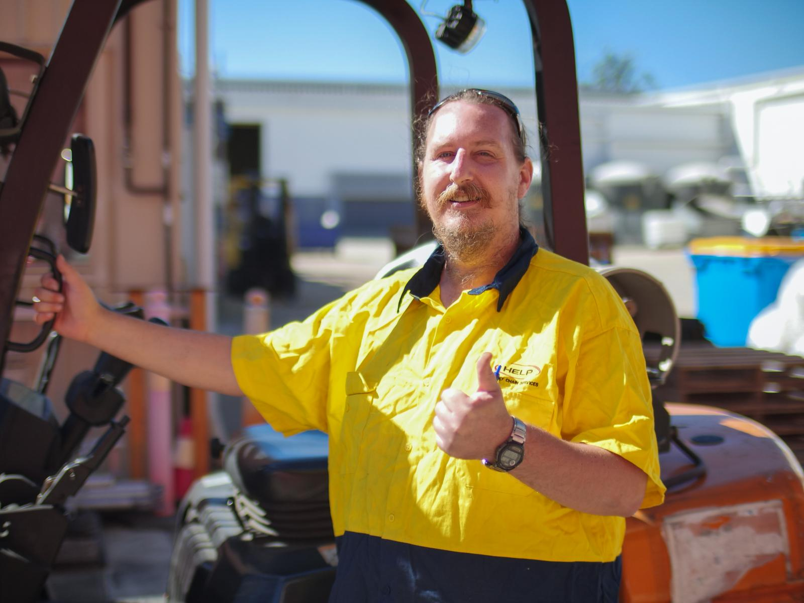 A young man in his 30's is wearing a neon yellow polo shirt standing in front of a forklift giving the thumbs up.